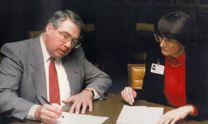 Dr. Carl Booberg (Director of the ALAV in 1991) signing over the ALAV Collection to Linda Watson