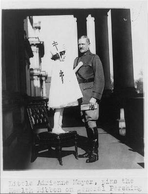 Little Adrienne Mayer pins the health ribbon on General John J. Pershing and sells him his Tuberculosis Christmas Seals, 1921