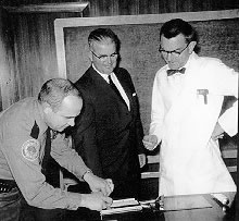 William Lamm, Hospital Director of Security, gets John Stacy's fingerprints while Dean Crispell observes the new ID card process